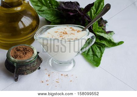 Classic European white sauce Bechamel in saucer with nutmeg basil and olive oil on white background. Bechamel sauce for traditional European dishes. Italian food concept. Selective focus. Copy space.