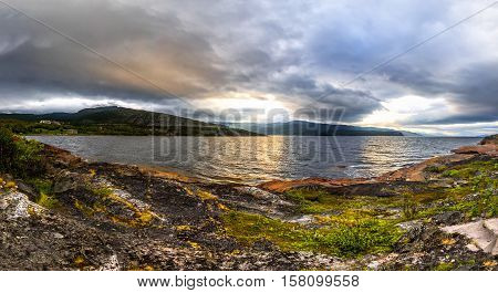 Scandinavian northern nature - rocky ground green moss. Beautiful sunset on Jiepmaluokta bay in the municipality of Alta in Norway. In Sami language the name Jiepmaluokta is