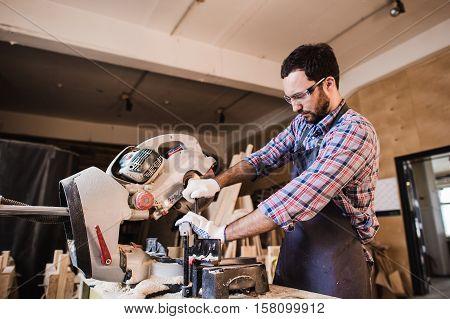 Carpenter Using Circular Saw for wood at his workshop.