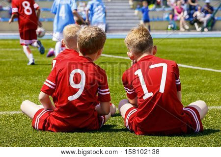 Two young soccer players sitting on sports field. Football soccer match for children. Boys playing football game on a school tournament.