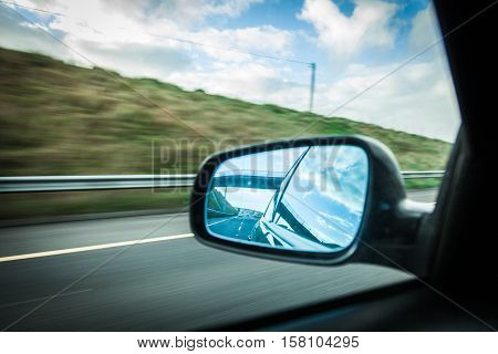 car on the road with motion blur background and rear view mirror