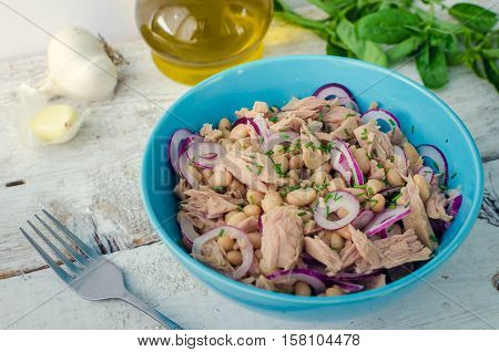 Tuna salad with white beans and red onions in a bowl with basil leaves on white old wooden background. Rustic style. Italian cuisine concept. Healthy food. Selective focus.