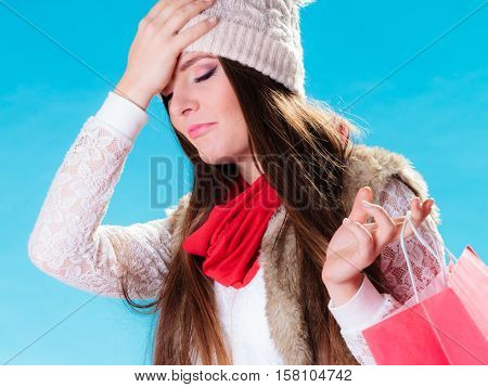 Last minute christmas shopping. Young worried stressed woman with hand on head holding paper bag on blue