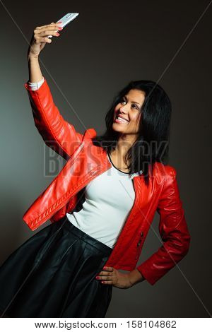 Technology and communication concept. Young attractive fashionable woman in red jacket using her mobile phone to take selfie photo.