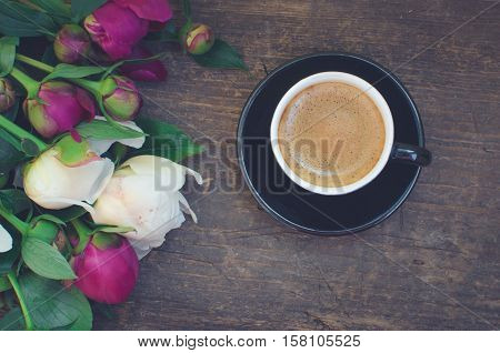 Coffee and flowers peony. A cup of coffee and Peonies on a wooden table. Breakfast on Mothers day Valentines Day or Womens day. Spring or summer background. Copy space. Top view. Toned image.