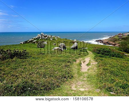 Path to a hill with crown of rocks by the sea
