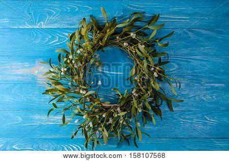 Christmas wreath with mistletoe on wood board. Christmas decoration