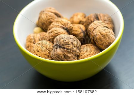 Walnuts In Green Ceramic Bowl In Close Up.