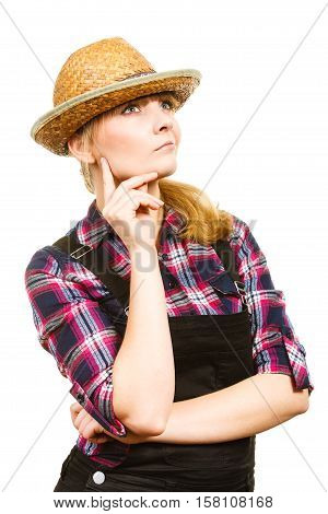 Gardening concept. Attractive woman in dungarees pink check shirt and sun hat making thinking face expression. Isolated background