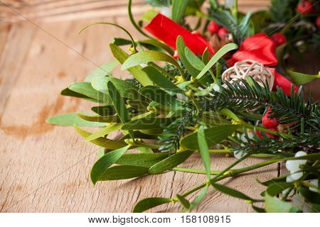 Green mistletoe on wood desk. Nature background. Christmas plant