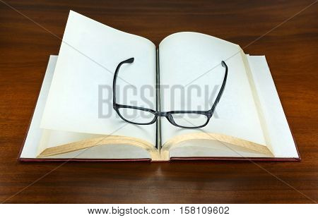 old blank book  open and eyeglasses put on paper page
