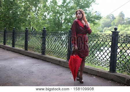 Cute beautiful girl in a red raincoat with an umbrella walks in the park