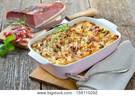Hearty potato gratin with parmesan cheese, cream and delicious cured bacon from South Tyrol served fresh from the oven poster
