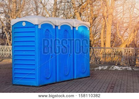 A row of bio toilets in public place hit by the sun