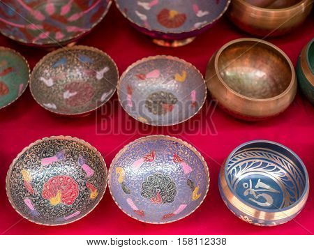 Metal and singing bowls displayed on red background