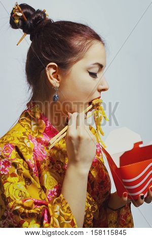 Beautiful woman eating chinese fastfood over white background