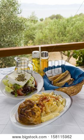 Greek food classic veal stifada with pasta Greek salad crusty bread with house wine as photographed in Logaras Paros Cyclades Greece