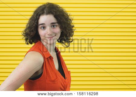 young woman brown curly hairs wearing orange shirt on yellow stripe background