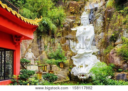 Red Roof In Chinese-style And A White Buddhist Statue On Background Of Small Waterfall In A Garden