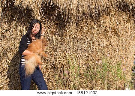 portrait thai woman and pomeranian with straw