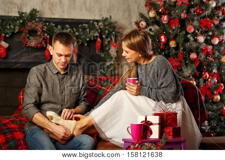 Loving couple and Christmas. Boyfriend wears woolen knit socks on the feet of his girlfriend. In the background a beautiful Christmas tree.