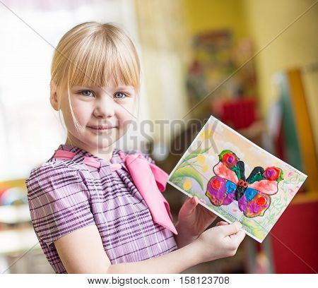 Portrait Of Cheerful Smiling Girl Holding A Bright Colorful Picture Of Butterfly Painted Colors And