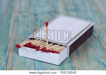 Red Matchbox and candle on color wood background