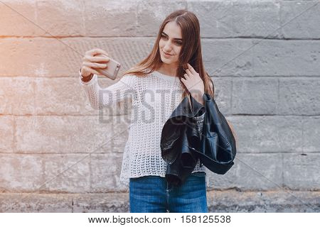 beautiful girl on the street using cell phones, a tablet and walks