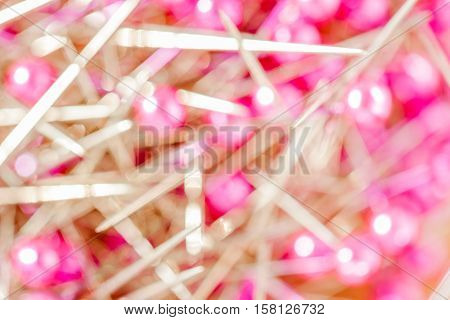 Abstract blurred photo of colorful pink sewing pins pile.