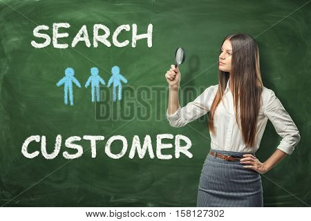 A beautiful businesswoman standing and looking through the magnifying glass near the green wall with the words 'search customer' and tiny blue humans drawn on it. Account manager. Business expansion. Search of opportunities. CRM.