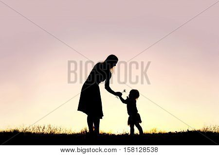 Silhouette Of Baby Girl Giving Mom Flower At Sunset