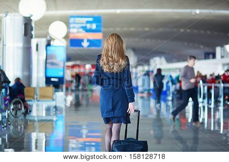 Young woman in international airport walking with her luggage back view. Flight attendant going to meet her crew
