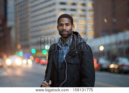 Portrait of African American man listening to music in the city photographed in NYC.