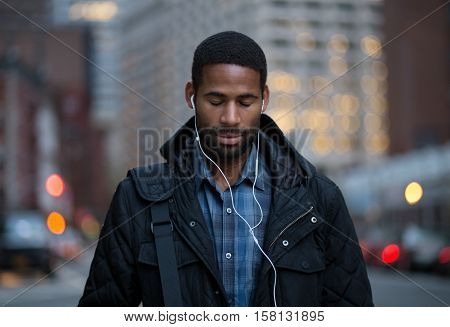 Portrait of African American man listening to music and taking in before work. Photographed in NYC 2016.