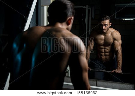 Muscular Man After Exercise Resting In Gym