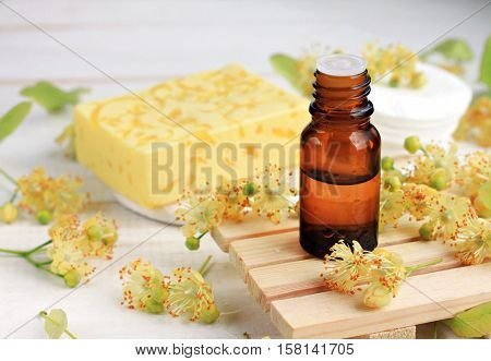 Botanical beauty care cosmetic products. Fresh yellow Tilia basswood blossom, essential oil bottle, handmade cleansing soap bar.