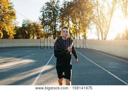 Runner practicing run on athletics running track. Sprinter training for marathon outdoor at sunset. Young man evening jog.