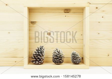 Still life of pine cones with snow in wooden square box. Christmas decoration. Pine cones in box of wooden pine.