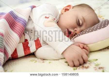 Cute newborn baby six months old in fashionable clothes sleeps