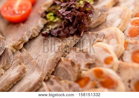 Assortment of sliced ham on a plate decorated with salad leaves