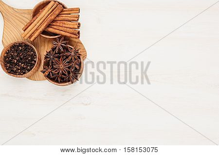 Spices - aniseed cinnamon cloves in wooden bowls on a wood white background. Spicy seasonings for cooking. Top view.