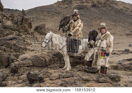 Thailand Tourist In Mongolia Traditionally Riding Horse With Kazakh Eagle Hunter In A Desert Mountai