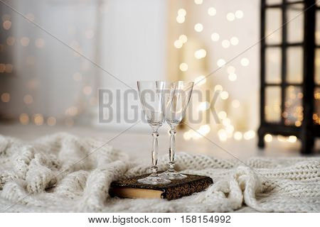 Beautiful two glasses of champagne standing on the table in the background of a blurred room with a decorated Christmas tree and fireplace. Soft focus.