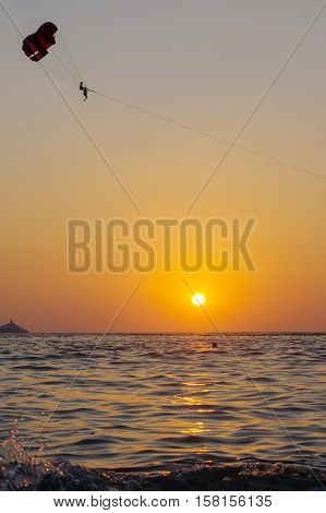 a Parasailing silhouette in beautiful sky over the sea water ocean at orange and red sunset Phuket Island Thailand