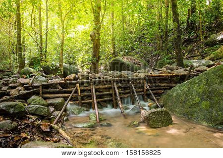 Wooden weir in rain forest Thailand, local water management, irrigation, mossy forest, moss and lichen, moss on rocks, Soft focus due to long exposure