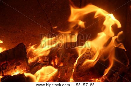 Red-hot coals with blue flame in an oven