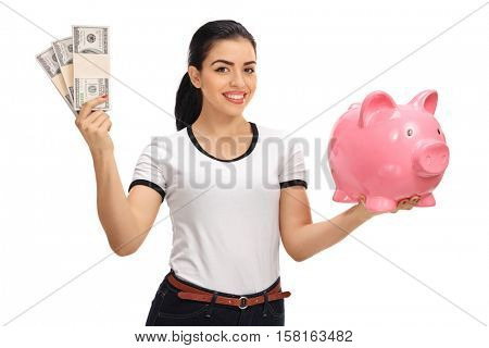 Young woman holding bundles of money and a piggybank isolated on white background
