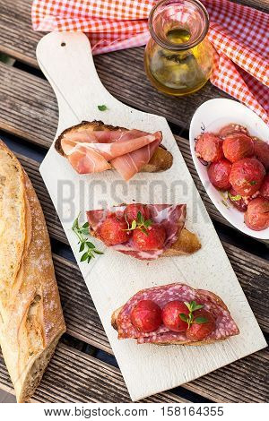 Italian bruschettas with ham prosciutto coppa salami and cherry tomatoes