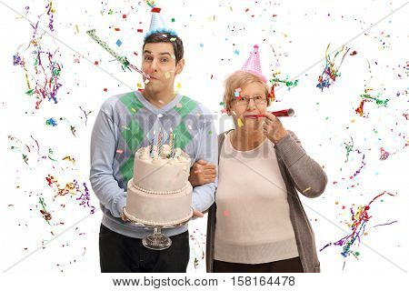Young man with a birthday cake and a mature woman blowing party horns isolated on white background