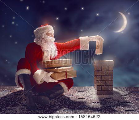 Merry Christmas and happy holidays! Santa Claus sitting on the roof of the house and puts the presents in the chimney. Christmas legend concept.